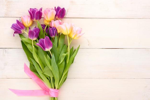 Bouquet de tulipes de printemps avec noeud rose sur fond de bois clair avec espace copie, fleurs violettes et roses