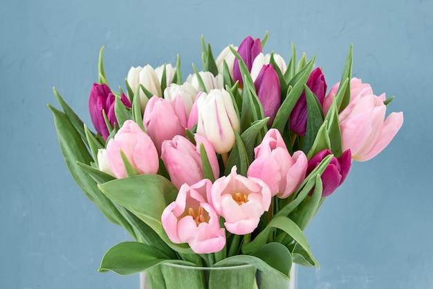 Bouquet de tulipes roses et blanches dans un vase en verre