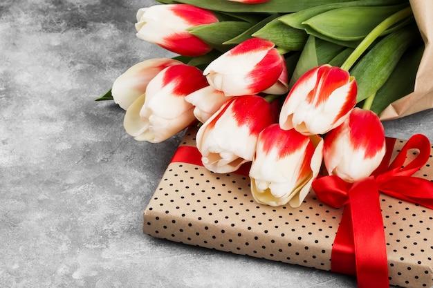 Bouquet de tulipes roses blanches sur fond gris. espace copie
