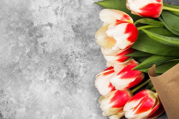 Bouquet de tulipes roses blanches sur fond gris. vue de dessus, espace copie