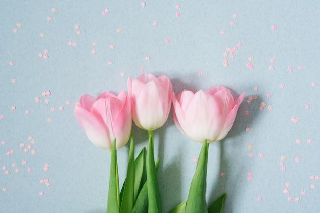 Un bouquet de tulipes roses sur bleu tendre avec des paillettes roses, à plat