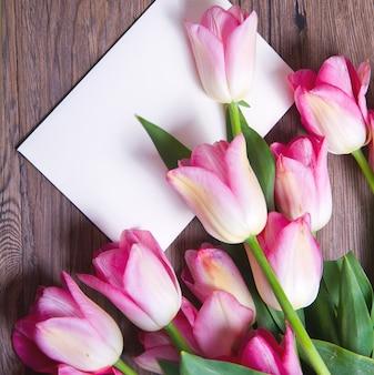 Bouquet de tulipes roses et carte postale sur bois