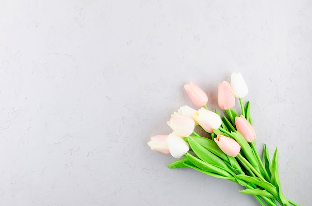 Bouquet de tulipes roses claires sur un béton gris