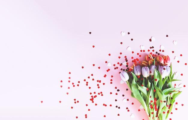 Bouquet de tulipes roses avec coeur décoratif saupoudre sur fond clair pastel doux. vue de dessus. fond festif de la saint-valentin.
