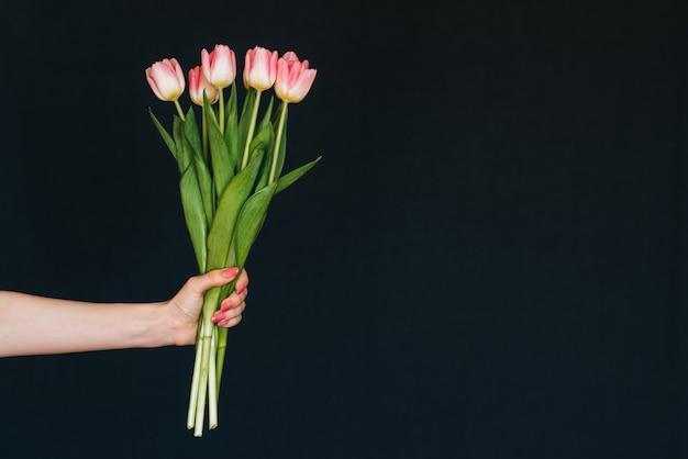 Bouquet de tulipes roses dans une main de femme