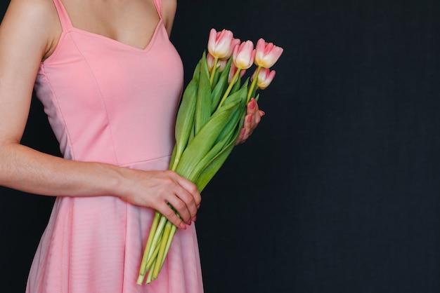 Bouquet de tulipes roses dans les mains de la femme