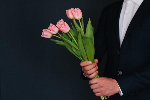 Bouquet de tulipes roses dans les mains des hommes dans un costume