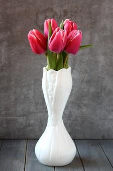 Bouquet de tulipes roses dans un vase blanc sur fond en bois