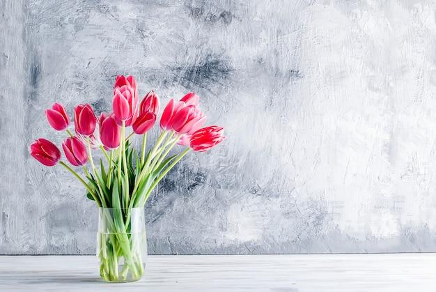 Bouquet de tulipes roses dans un vase en verre sur fond gris.