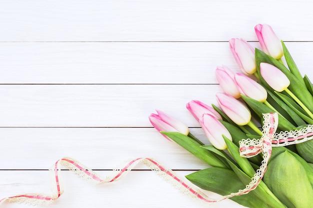 Bouquet de tulipes roses décorées avec un ruban sur un fond en bois blanc.