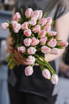 Bouquet de tulipes roses fraîches de printemps à la main, copy space