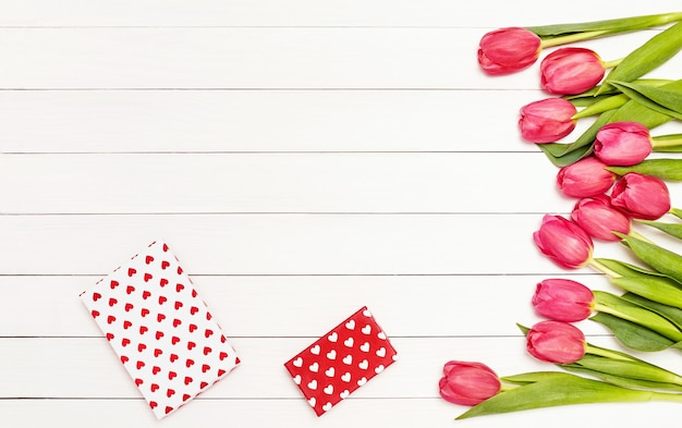 Bouquet de tulipes roses sur une table en bois blanche décorée de coffrets cadeaux.