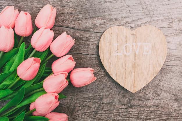 Bouquet de tulipes roses et une valentine en forme de coeur en bois, sur un fond en bois