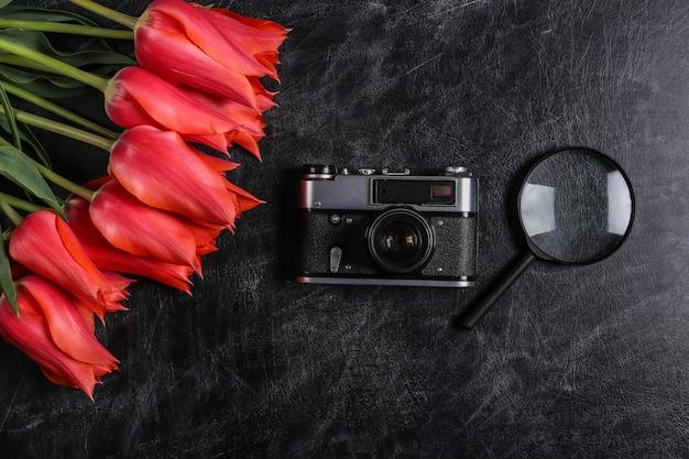 Bouquet de tulipes rouges, appareil photo, loupe sur fond de tableau noir