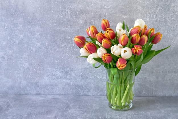 Bouquet de tulipes rouges et blanches dans un vase en verre sur fond gris. vacances