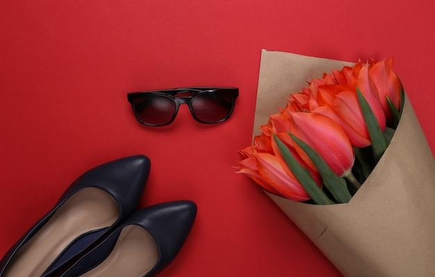 Bouquet de tulipes rouges et chaussures à talons hauts, lunettes de soleil sur fond rouge. fête des mères ou 8 mars, anniversaire. vue de dessus