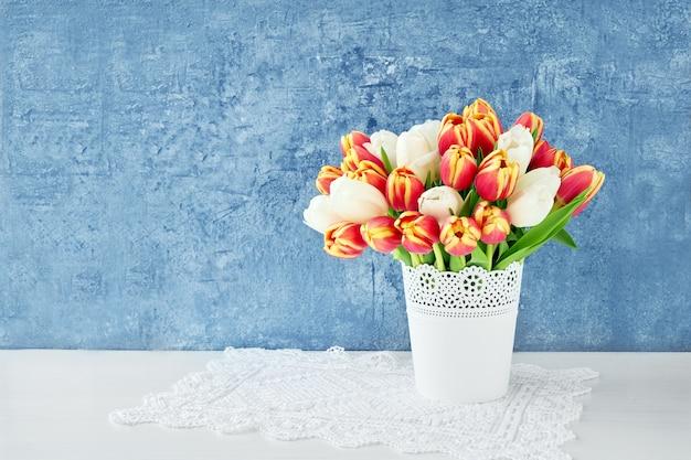 Bouquet de tulipes rouges dans un vase blanc sur bleu vif. vacances, espace copie