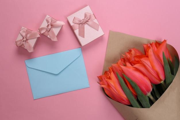 Bouquet de tulipes rouges avec enveloppe et coffrets cadeaux sur pastel rose