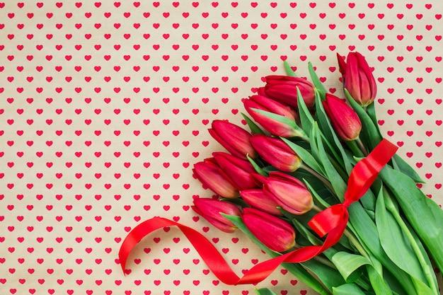 Bouquet de tulipes rouges sur fond de coeurs.