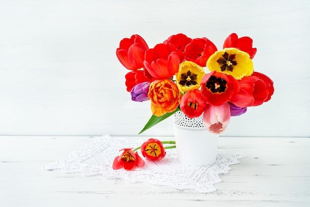 Bouquet de tulipes rouges et jaunes dans un vase blanc sur blanc. vacances, copiez l'espace.