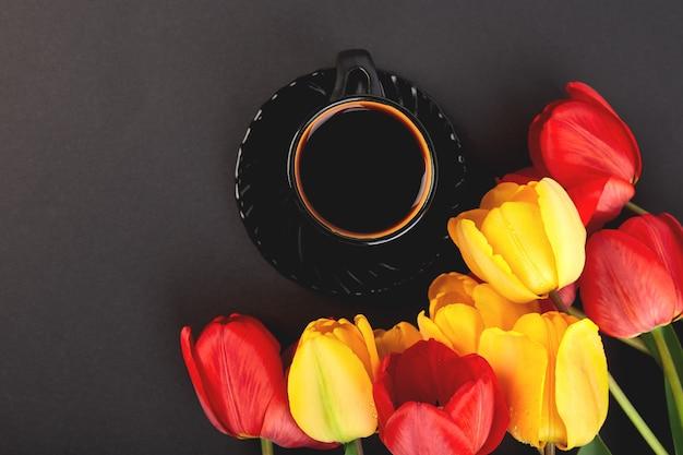 Bouquet de tulipes rouges et jaunes et une tasse de café. pose à plat