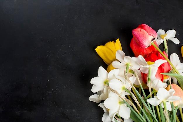 Bouquet de tulipes rouges, jonquilles et cadeau sur le fond noir