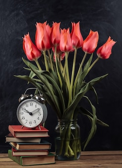 Bouquet de tulipes rouges et pile de livres avec réveil sur fond de tableau noir. école nature morte