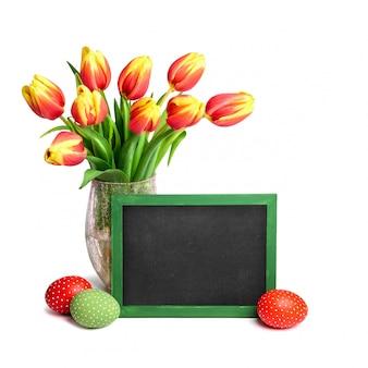 Bouquet de tulipes rouges avec des sommets jaunes, un tableau noir et des oeufs de pâques colorés sur blanc, espace de texte