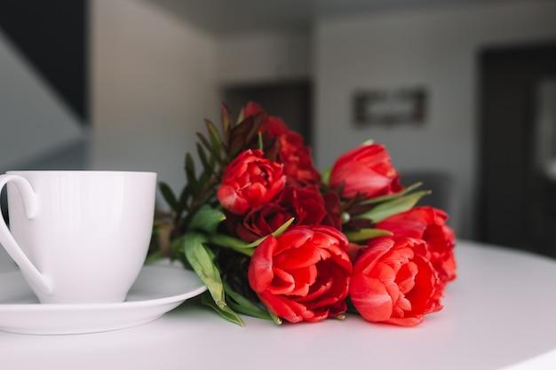 Un bouquet de tulipes rouges sur la table et une tasse de café blanche. concept pour une carte de voeux.