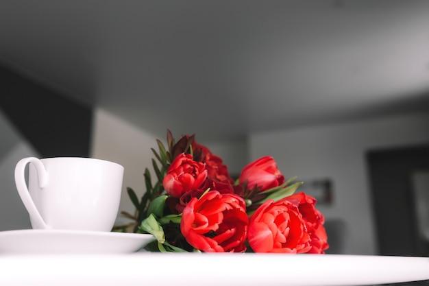 Un bouquet de tulipes rouges sur la table et une tasse de café blanche. concept de romantisme