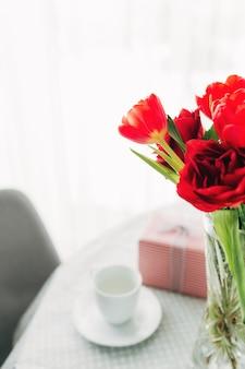 Bouquet de tulipes rouges sur table avec tasse à café blanche
