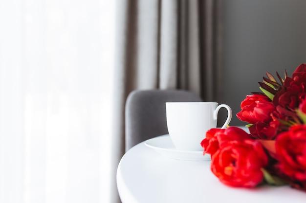 Bouquet de tulipes rouges sur table et tasse à café blanche
