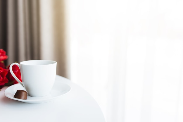 Bouquet de tulipes rouges sur table, tasse à café blanche.