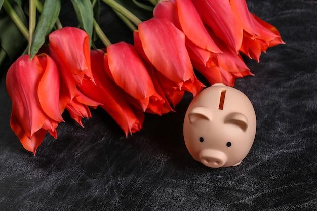 Bouquet de tulipes rouges et tirelire sur un fond de tableau