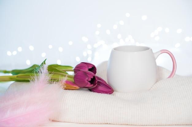 Un bouquet de tulipes, une tasse de café, des plumes roses et un pull sur fond clair à brûler