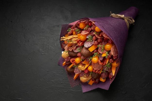 Bouquet unique pour un homme composé de saucisses, fromage, tomates et pain noir sur fond noir