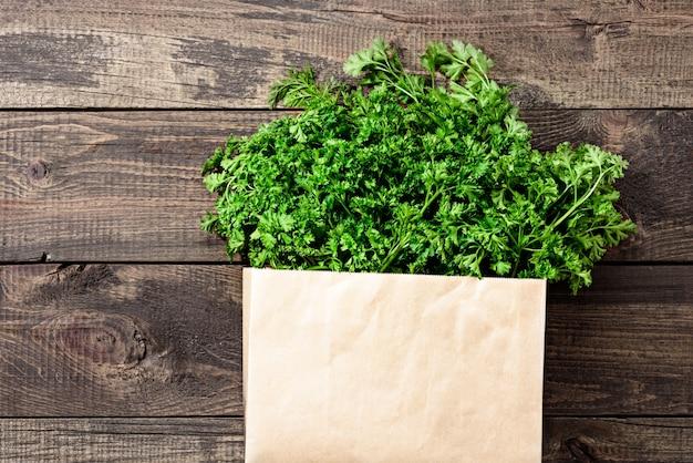 Bouquet de verdure fraîche dans un sac réutilisable écologique sur l'espace de copie de fond en bois
