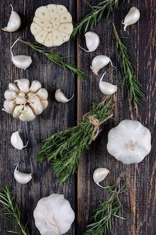Bouquets d'ail au romarin sur une table en bois foncé. vue de côté.