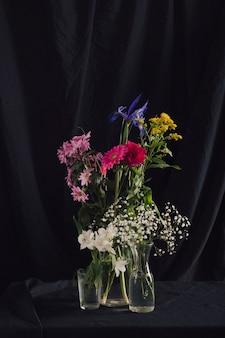 Bouquets de fleurs colorées dans des vases avec de l'eau