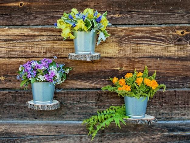 Bouquets de fleurs dans des pots en étain contre un mur en bois rustique.