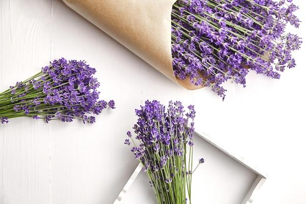 Bouquets de fleurs de lavande à plat sur une table en bois blanc