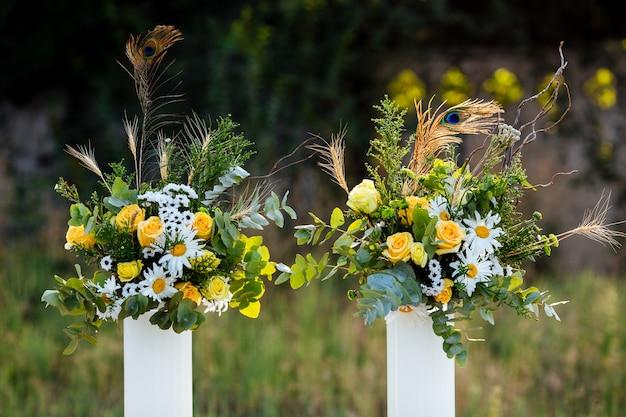 Bouquets de fleurs roses jaunes plumes de paon