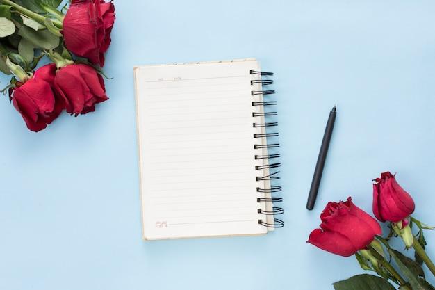 Bouquets de fleurs rouges près de cahier et stylo