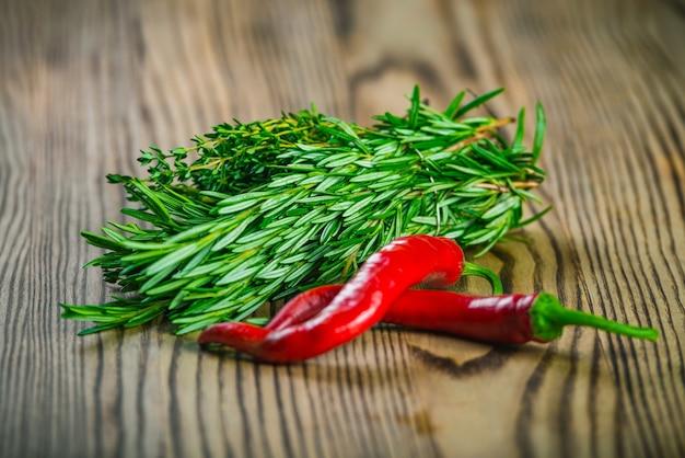 Bouquets d'herbes fraîches thym, salade et romarin, piments rouges sur planche de bois.