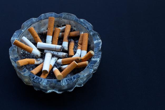 Des bourgeons de cigarettes dans un cendrier transparent sur l'obscurité.