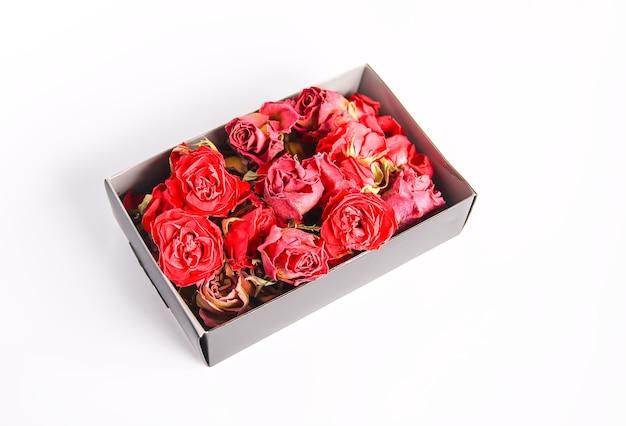 Bourgeons, fleurs et pétales séchés de rose rouge dans la boîte en carton ouverte