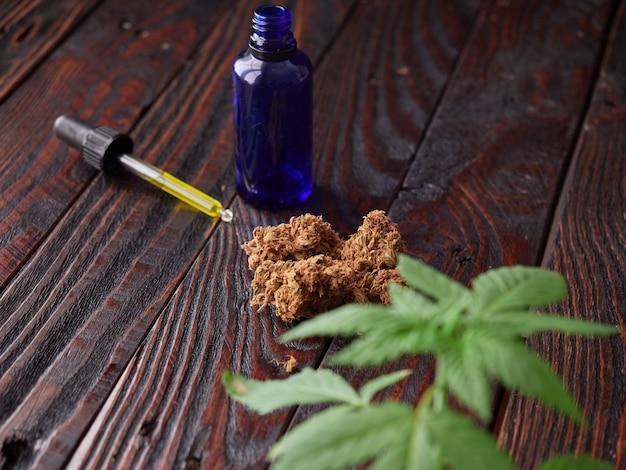 Bourgeons et huile de marijuana sur une table rustique