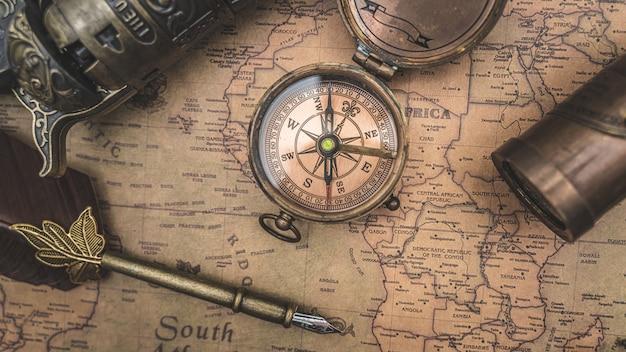 Boussole antique et plume sur la carte du vieux monde