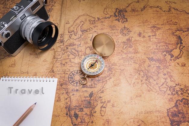 Boussole et appareil photo vintage sur la carte pour la planification de voyage