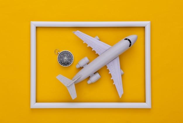 Boussole et avion dans un cadre blanc sur fond jaune. vue de dessus. concept de voyage minimalisme. mise à plat